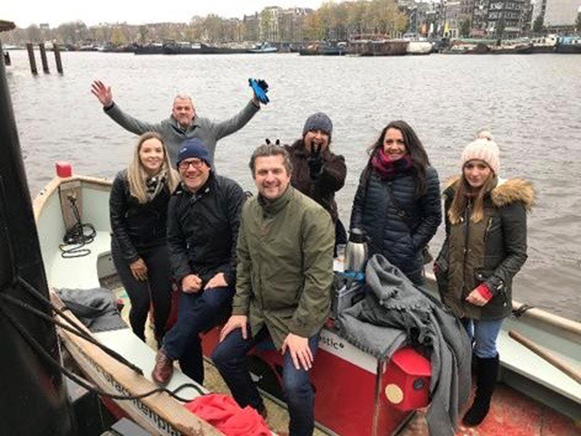 Team of people on boat in Amsterdam about to go fishing for plastic in amsterdam
